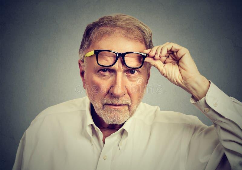 Hombre mayor escéptico con los vidrios que le miran fotos de archivo libres de regalías