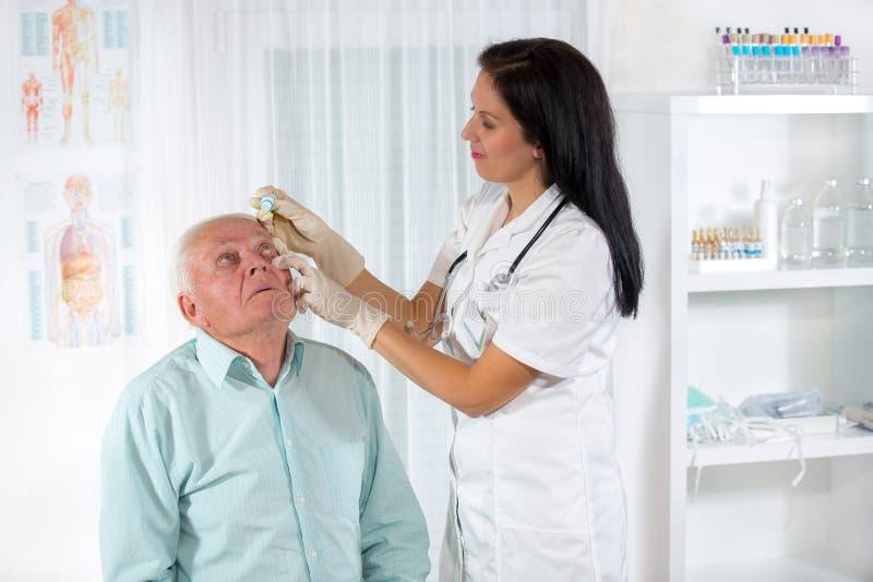 Hombre mayor examinado por un oftalmólogo fotos de archivo