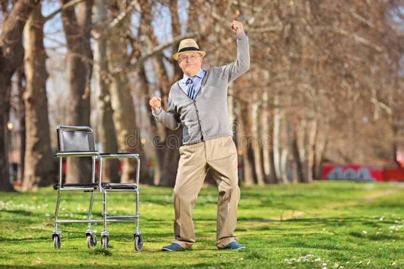 Hombre mayor extático que se levanta de una silla de ruedas imágenes de archivo libres de regalías