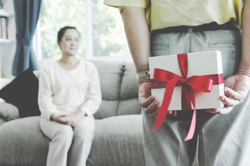 Hombre mayor feliz de los pares asombrosamente su novia con un regalo en el sofá en casa fotos de archivo