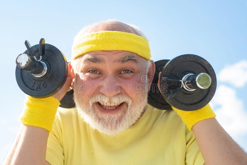 Hombre mayor feliz del deporte que ejercita con pesa de gimnasia de elevación en fondo del cielo azul Aislado, espacio de la copi fotos de archivo