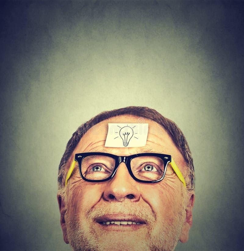 Hombre mayor feliz del retrato en vidrios con la bombilla de la idea que mira para arriba imagen de archivo libre de regalías