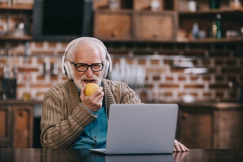 Hombre mayor feliz en auriculares que come la manzana imagen de archivo libre de regalías