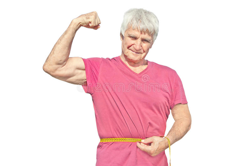 Hombre mayor feliz en camisa roja con la cinta métrica El hombre mayor muestra para poseer el bíceps del brazo aislado en el fond foto de archivo
