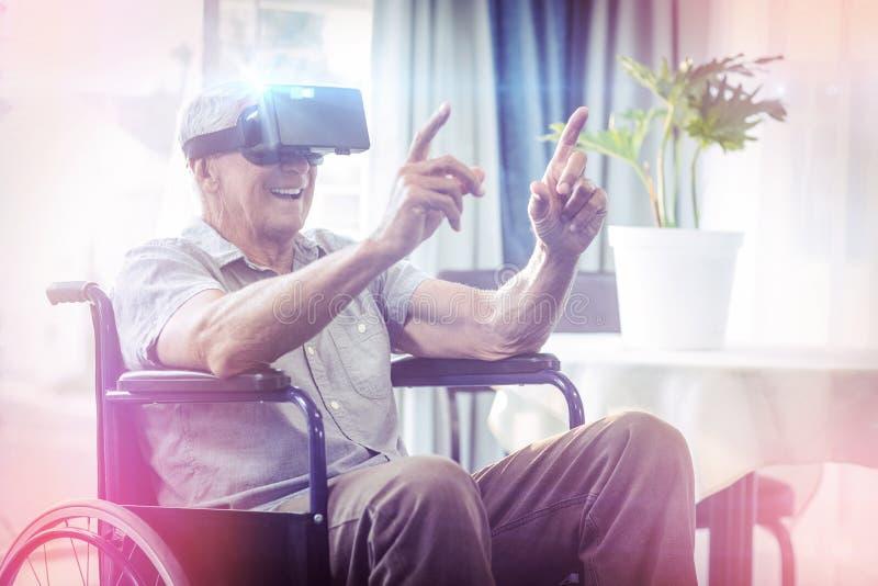 Hombre mayor feliz en la silla de ruedas usando las auriculares de VR imagen de archivo