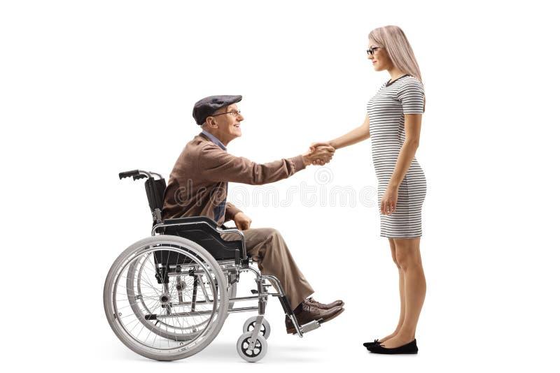 Hombre mayor feliz en una silla de ruedas que sacude las manos con una mujer joven imagenes de archivo