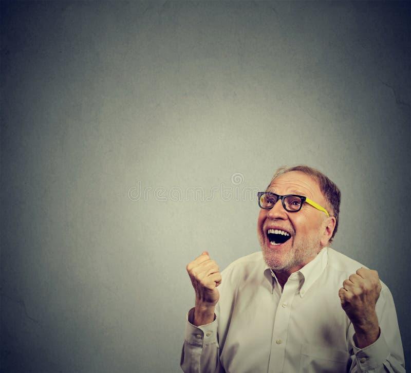 Hombre mayor feliz que celebra éxito fotografía de archivo