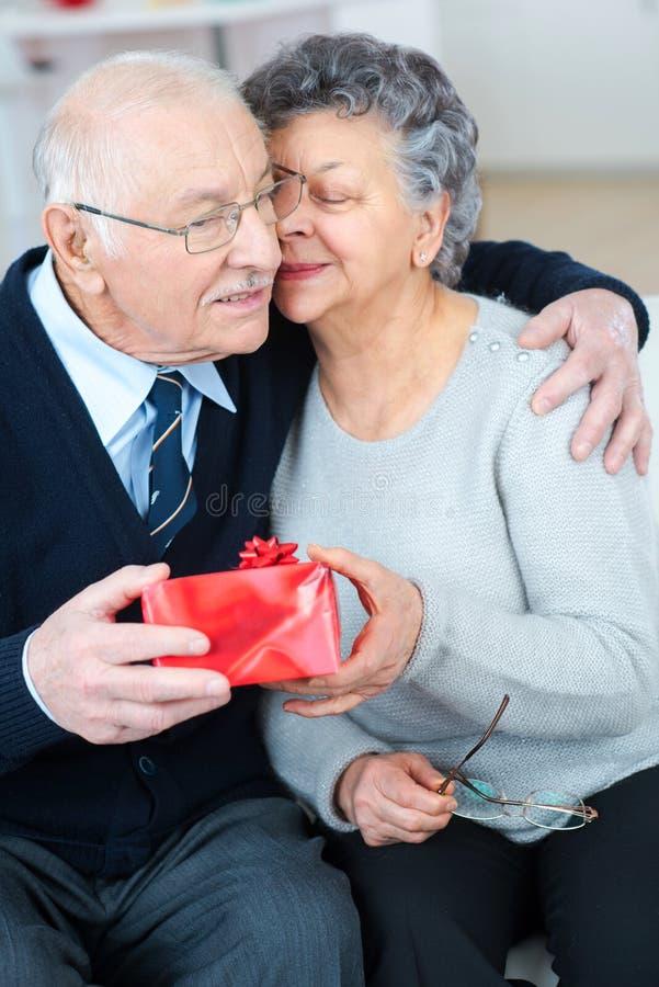 Hombre mayor feliz que da el regalo a la esposa fotografía de archivo libre de regalías