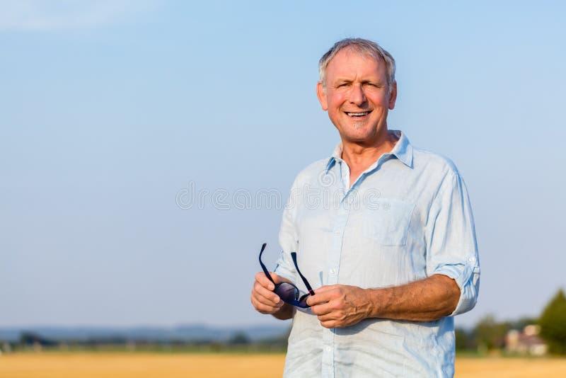 Hombre mayor feliz que disfruta del retiro durante un día de verano adentro fotos de archivo