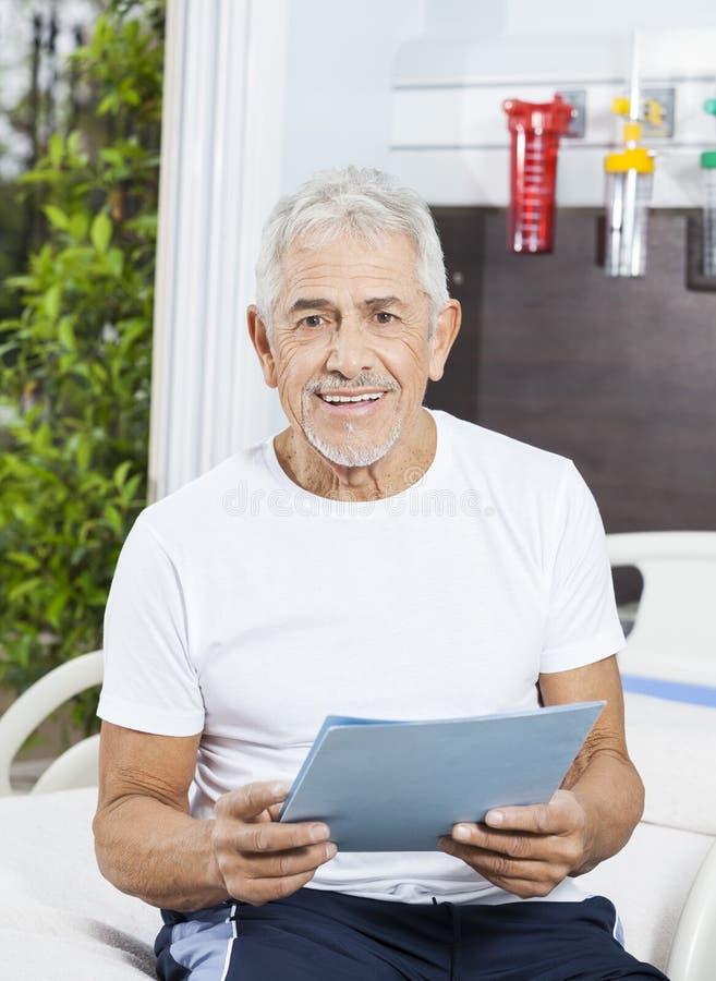 Hombre mayor feliz que lleva a cabo informe en el centro de rehabilitación imagen de archivo libre de regalías