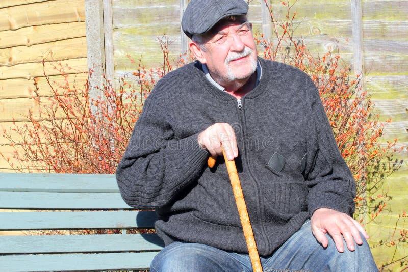 Hombre mayor feliz que se sienta en un banco imagenes de archivo
