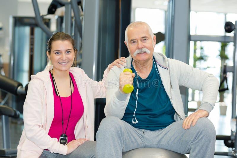 Hombre mayor feliz que sonríe con el instructor personal foto de archivo libre de regalías