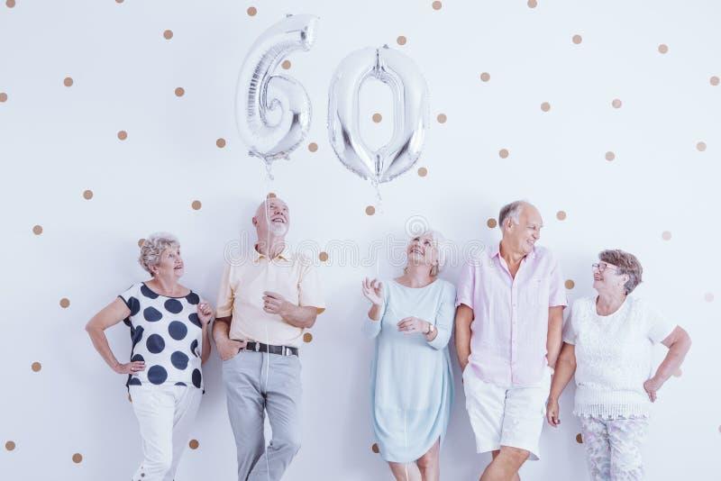 Hombre mayor feliz y mujer que sostienen los globos de plata foto de archivo