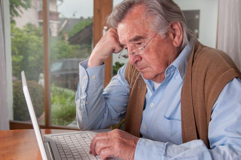 Hombre mayor frustrado con el ordenador portátil fotos de archivo libres de regalías