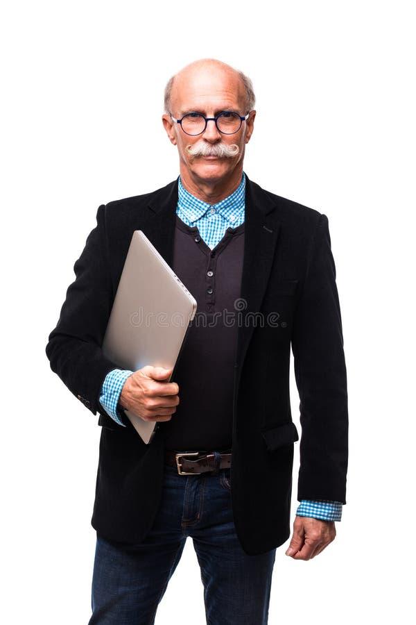 Hombre mayor hermoso que se coloca con el ordenador portátil en el fondo blanco fotografía de archivo