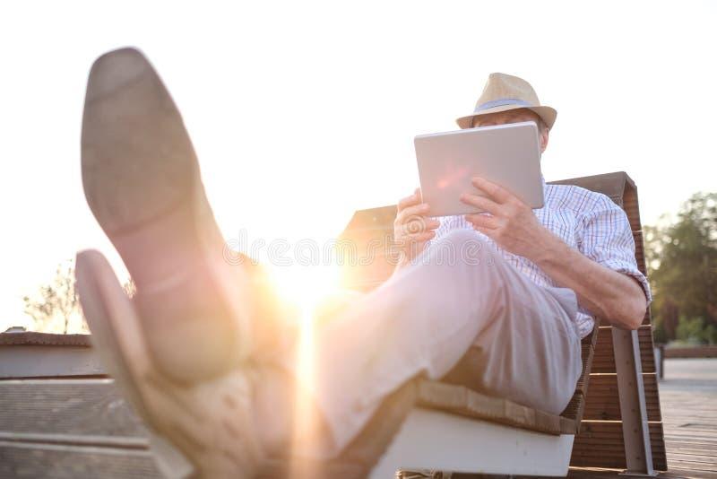 Hombre mayor hispánico en tableta de la lectura del sombrero del verano en espacio de la copia del parque foto de archivo libre de regalías