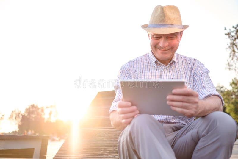 Hombre mayor hispánico en tableta de la lectura del sombrero del verano en espacio de la copia del parque imágenes de archivo libres de regalías