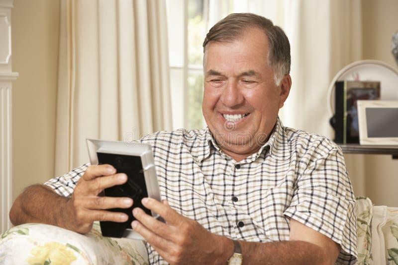 Hombre mayor jubilado feliz que se sienta en la fotografía de Sofa At Home Looking At fotos de archivo