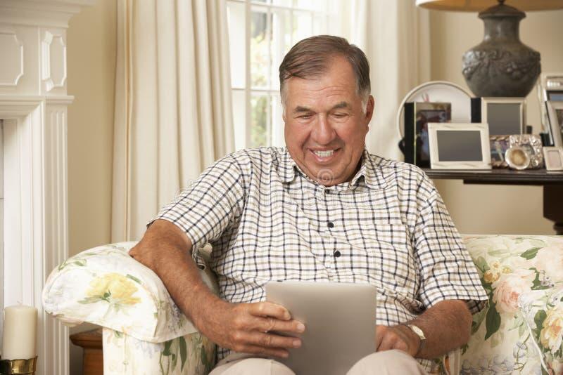 Hombre mayor jubilado que se sienta en el ordenador de Sofa At Home Using Tablet imagenes de archivo