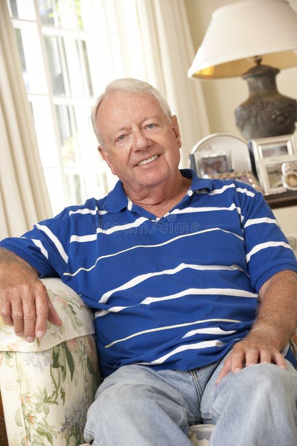 Hombre mayor jubilado que se sienta en Sofa At Home imagen de archivo