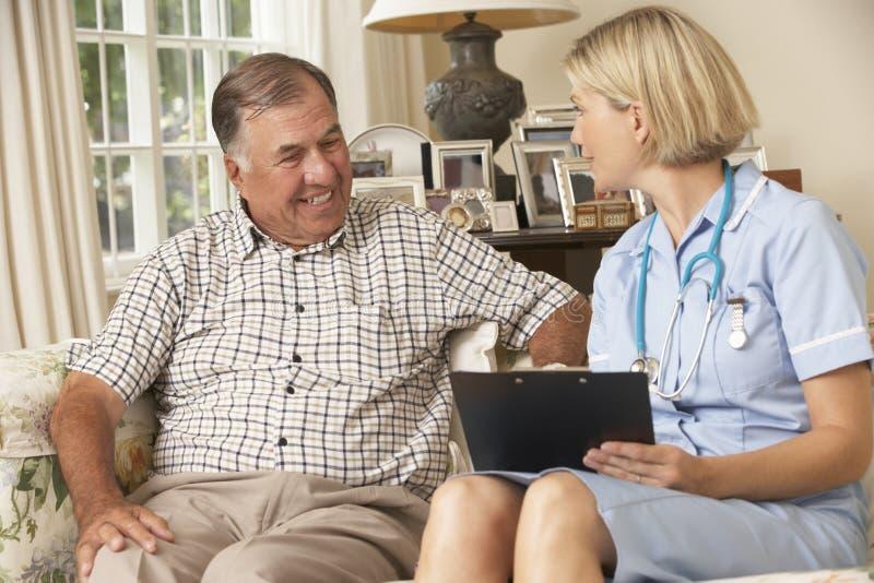 Hombre mayor jubilado que tiene revisión médica con la enfermera At Home imágenes de archivo libres de regalías