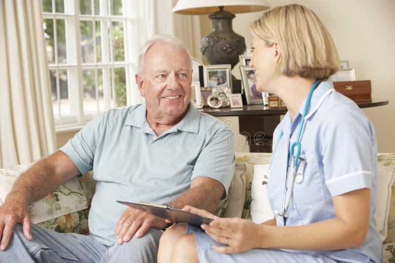 Hombre mayor jubilado que tiene revisión médica con la enfermera At Home imagen de archivo libre de regalías