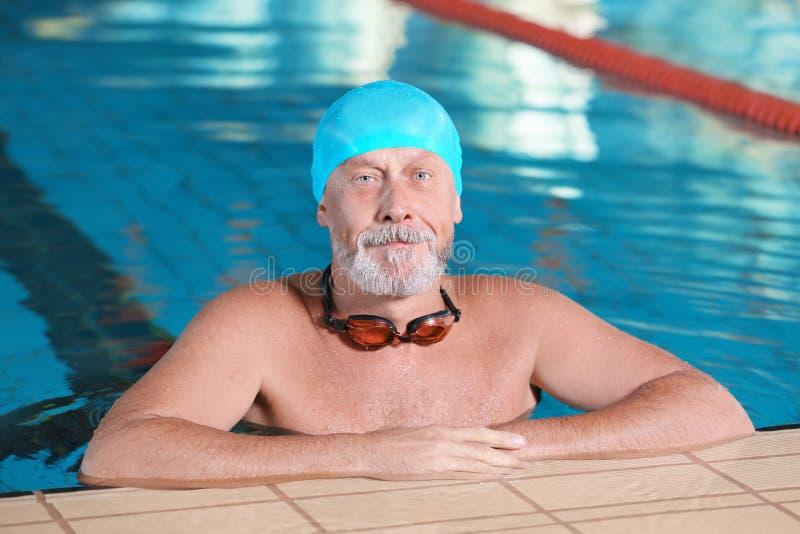 Hombre mayor juguetón en piscina interior foto de archivo libre de regalías