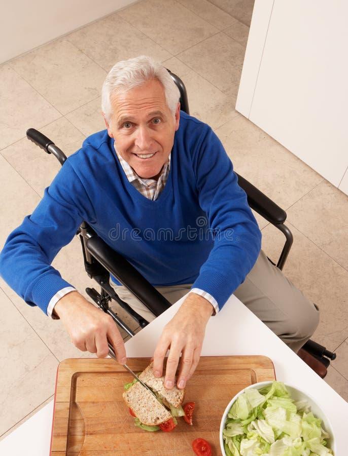 Hombre mayor lisiado que hace el emparedado en cocina fotos de archivo