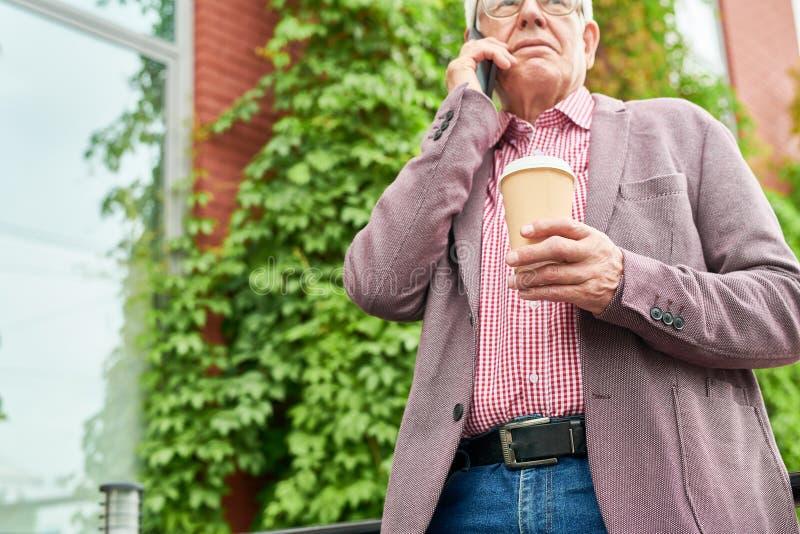 Hombre mayor moderno que habla por el teléfono al aire libre foto de archivo