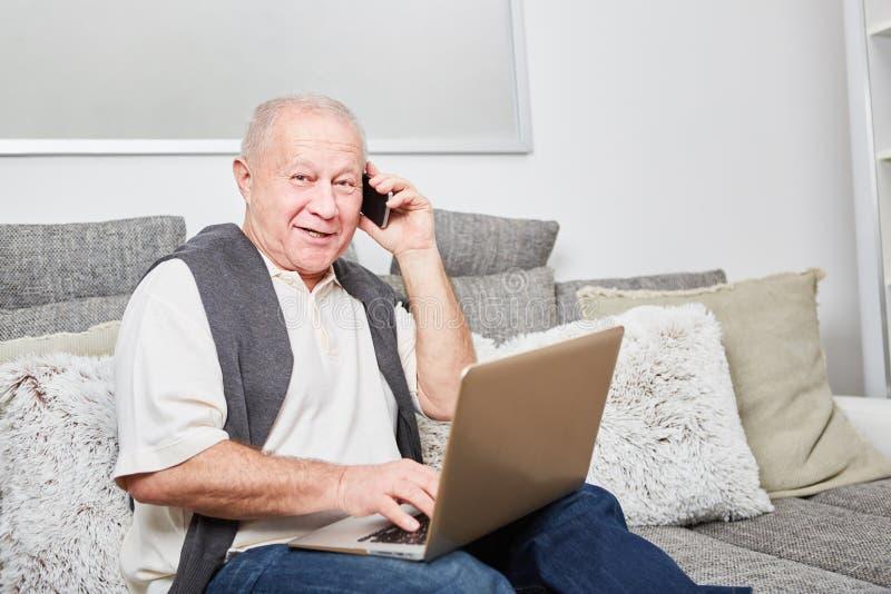 Hombre mayor moderno que llama con smartphone imagenes de archivo