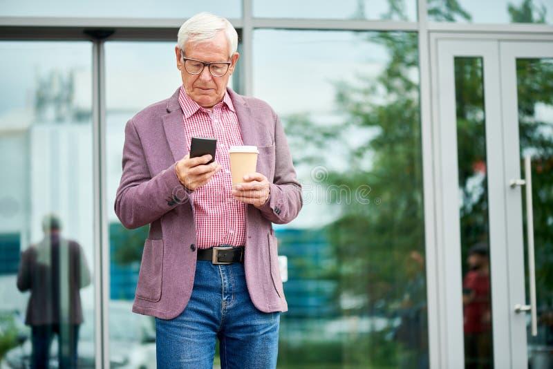 Hombre mayor moderno que manda un SMS al aire libre fotos de archivo