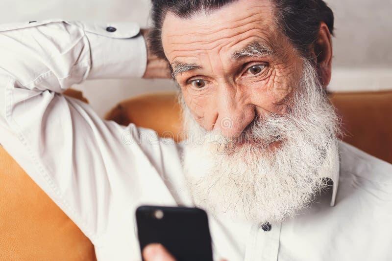 Hombre mayor moderno que mira en su Smartphone foto de archivo libre de regalías