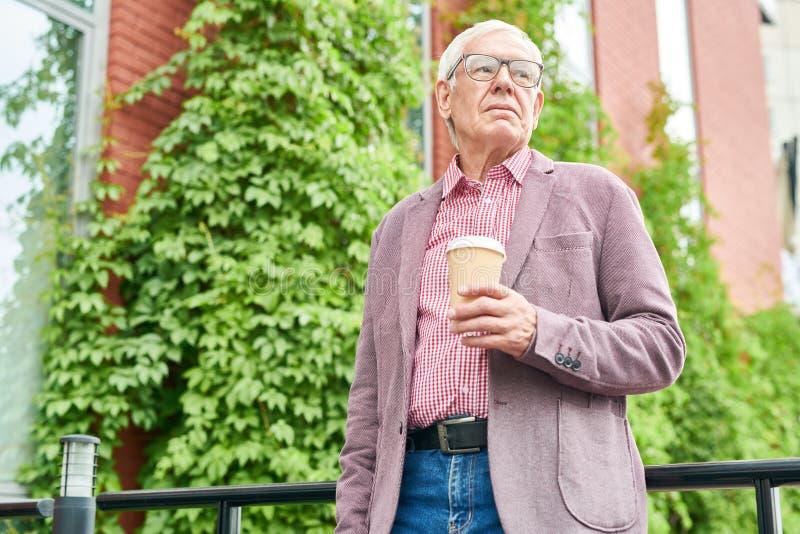 Hombre mayor moderno que presenta al aire libre fotografía de archivo