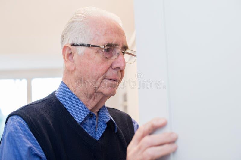Hombre mayor olvidadizo con la demencia que mira en armario en casa imagenes de archivo