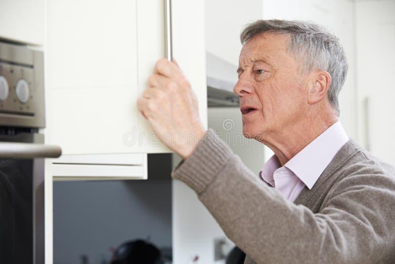 Hombre mayor olvidadizo que mira en armario imagen de archivo