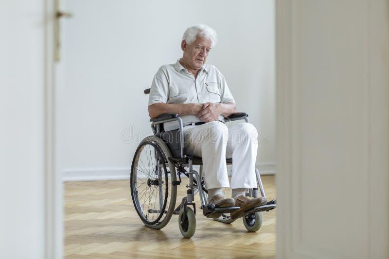 Hombre mayor paralizado triste en la silla de ruedas que se sienta solamente en casa fotografía de archivo