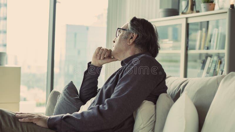 Hombre mayor pensativo en casa foto de archivo