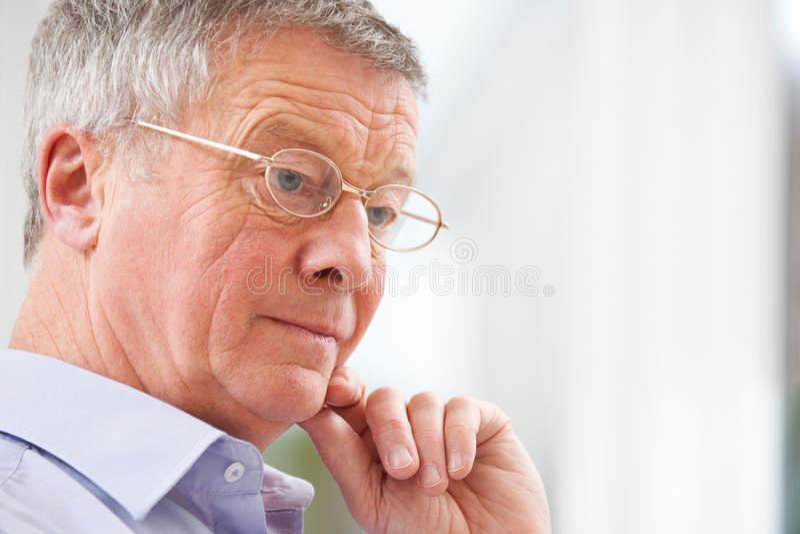 Hombre mayor pensativo en casa imagenes de archivo