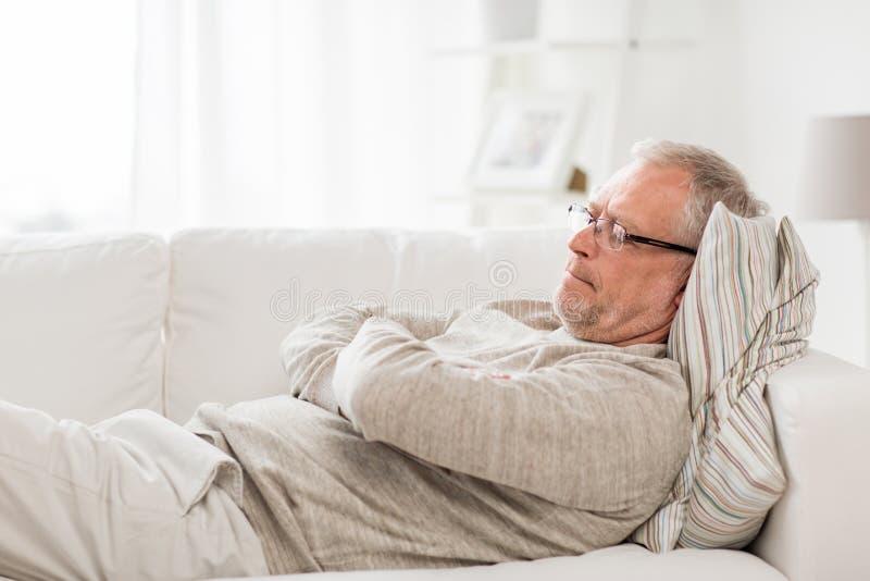 Hombre mayor pensativo que miente en el sofá en casa fotos de archivo