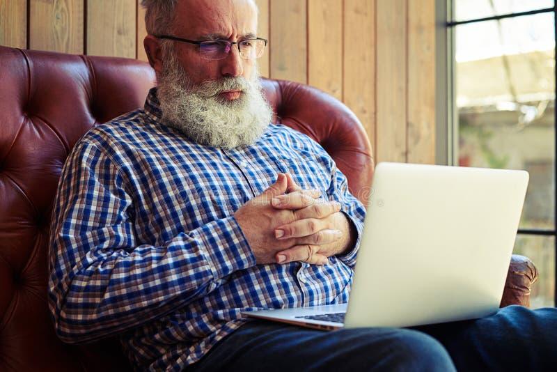 Hombre mayor pensativo que mira el ordenador portátil en casa foto de archivo