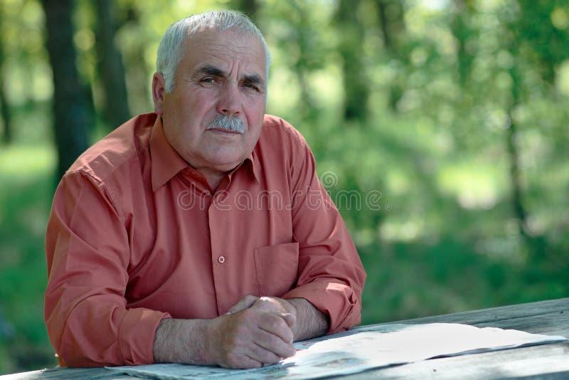 Hombre mayor pensativo que mira la cámara fotografía de archivo libre de regalías