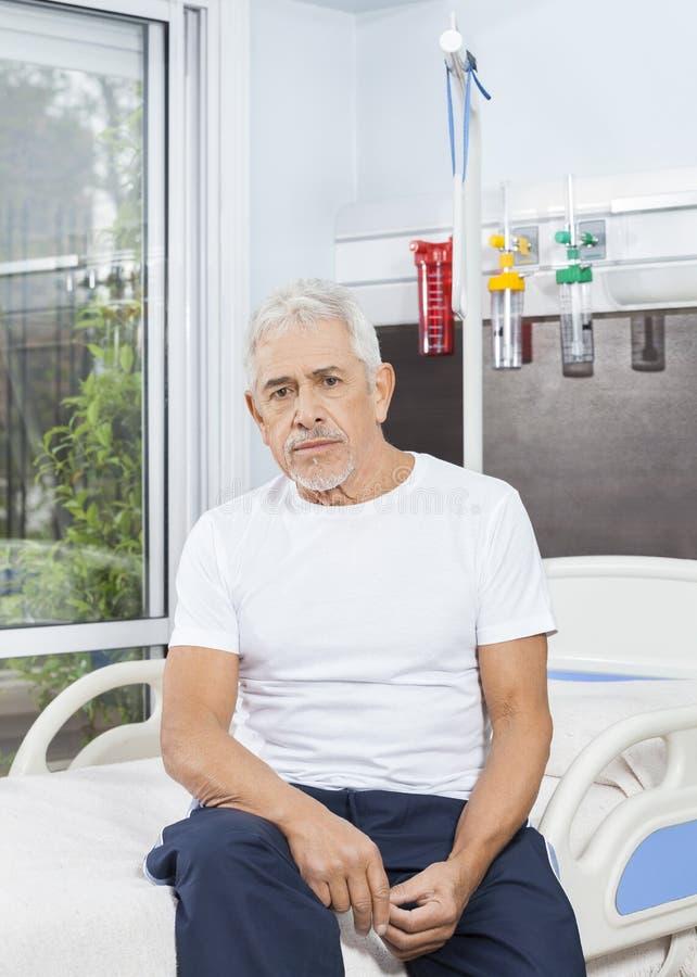 Hombre mayor pensativo que se sienta en cama en el centro de rehabilitación fotografía de archivo libre de regalías