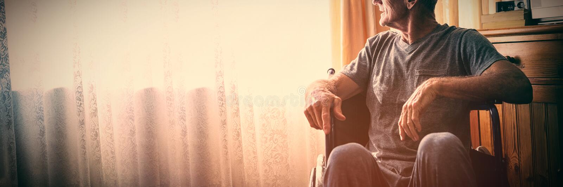 Hombre mayor pensativo que se sienta en la silla de ruedas en clínica de reposo imagen de archivo
