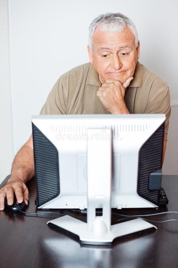 Hombre mayor pensativo que usa el ordenador en sala de clase foto de archivo