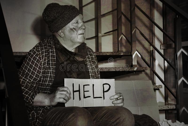 Hombre mayor pobre con AYUDA de la muestra de la cartulina en las escaleras fotos de archivo libres de regalías