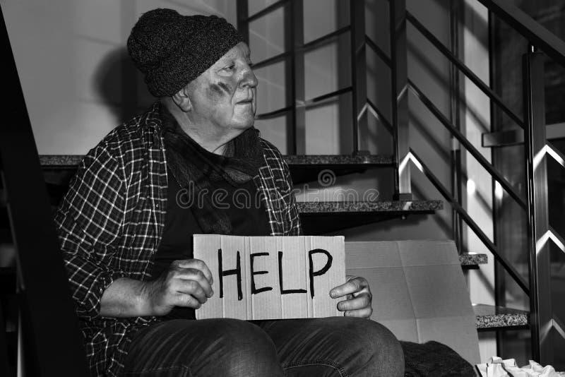 Hombre mayor pobre con AYUDA de la muestra de la cartulina en las escaleras dentro fotos de archivo libres de regalías
