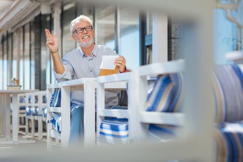 Hombre mayor positivo que levanta su mano imagen de archivo