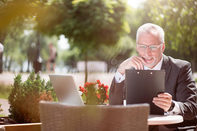 Hombre mayor positivo que se sienta en la tabla fotografía de archivo