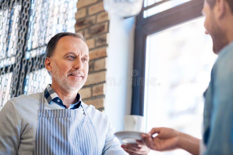 Hombre mayor positivo que sostiene la taza de café imágenes de archivo libres de regalías