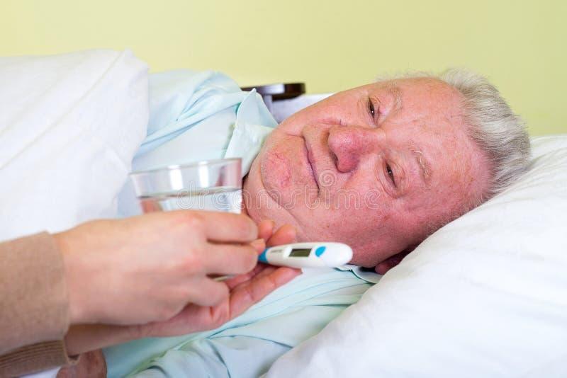 Hombre mayor postrado en cama que tiene temperatura alta foto de archivo libre de regalías